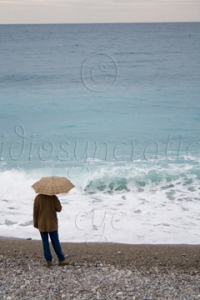 Watching - Man with Umbrella on Stormy Beach