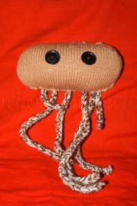 Knitted E-Coli Toy on Red Background
