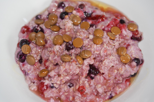 A Bowful of Pink Porridge with Mixed Berries, Chocolate Drips and Honey