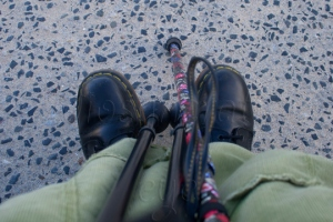 Pair of black DM boots under a long green corduroy skirt with three walking sticks resting against