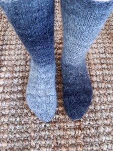 Two feet wearing thicker handknit socks in a range of greys to charcoal on a jute woven rug