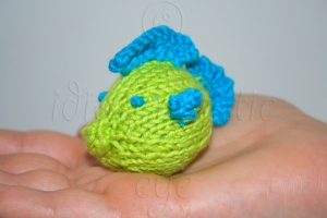 A Little Green and Blue Handknit Fish on a Hand
