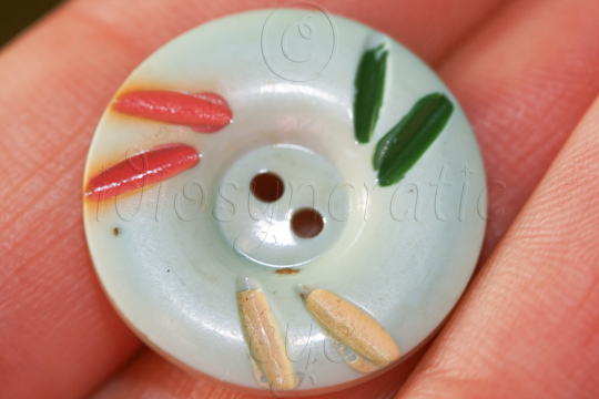 Pale turquoise plastic button with coloured dashes