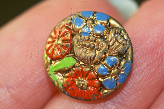 Metal button with flower shapes, some painted