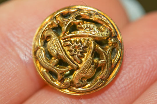 Gold-coloured metal button with an openwork design of three birds