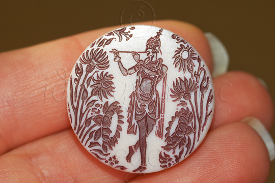 Brown and white plastic button with an etched 'Indian' design