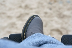 Grey DM shoes propped up against raised wheelchair footplates under a wool blanket at a sandy beach