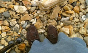 Suede moccasins under a blue green lighter corduroy skirt on a pebble beach with two walking sticks nearby